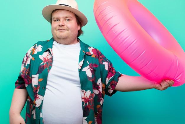 Giovane uomo di grandi dimensioni con una ciambella gonfiabile contro la parete piana