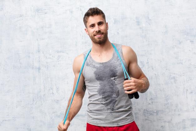 Giovane uomo di handosme contro la parete con una corda di salto. concetto di sport