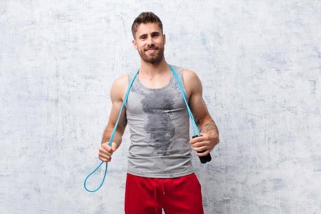 Giovane uomo di handosme contro la parete piana di colore con una corda di salto. concetto di sport