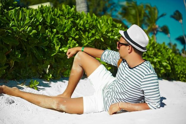 Giovane uomo di modello maschio alla moda che si trova sul cappello d'uso dell'estate dei pantaloni a vita bassa della sabbia della spiaggia