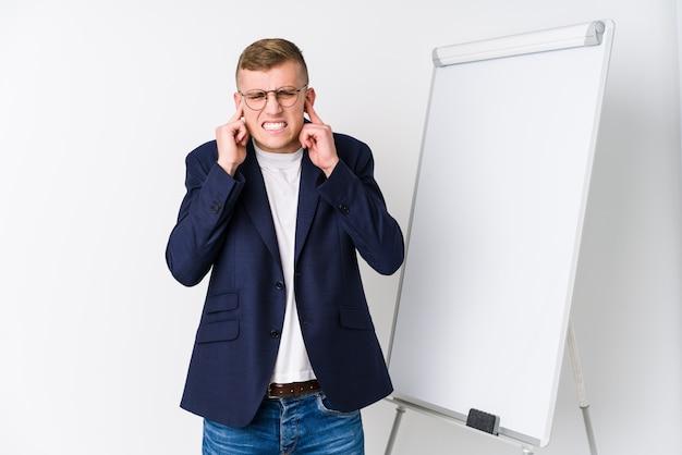 Giovane uomo di preparazione che mostra un bordo bianco che copre le orecchie di mani.