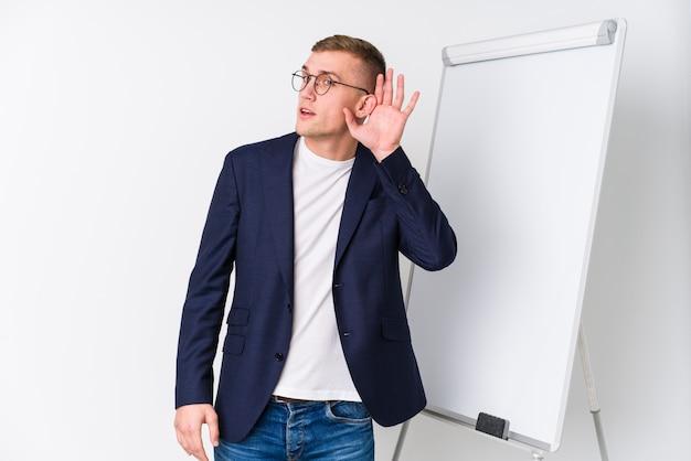 Giovane uomo di preparazione che mostra un bordo bianco che prova ad ascoltare un gossip.