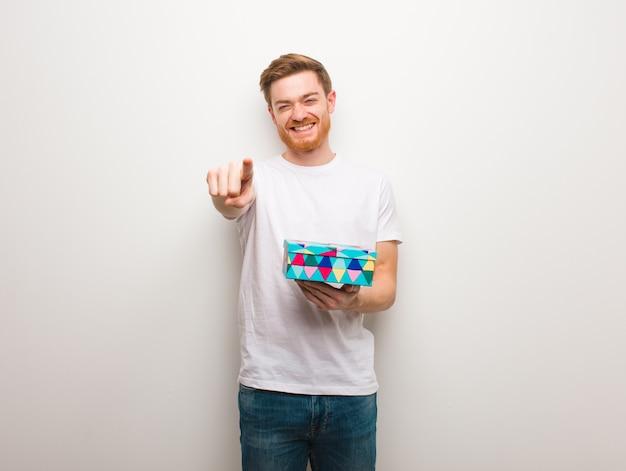 Giovane uomo di redhead allegro e sorridente che indica la parte anteriore. con in mano una confezione regalo.
