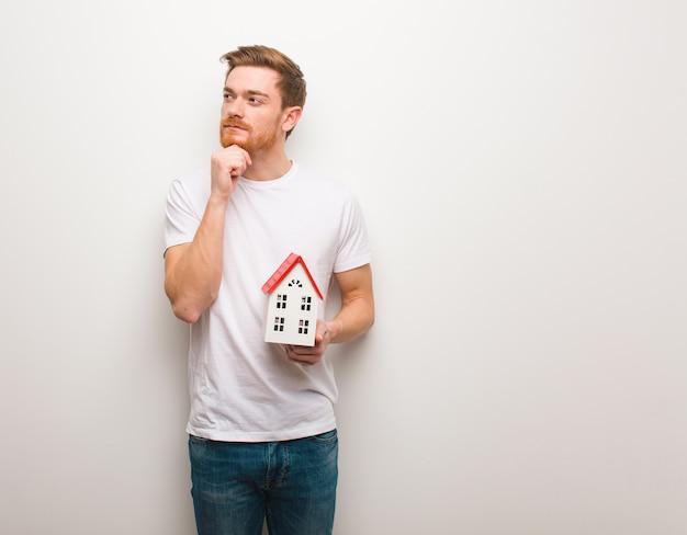 Giovane uomo di redhead che dubita e confuso. in possesso di un modello di casa.