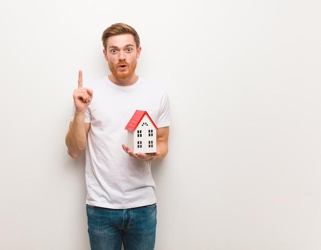 Giovane uomo di redhead che ha una grande idea, concetto di creatività. in possesso di un modello di casa.