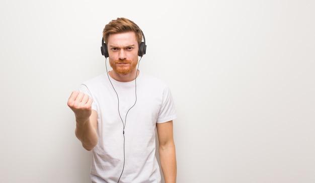 Giovane uomo di redhead che mostra pugno alla parte anteriore, espressione arrabbiata. ascoltando musica con le cuffie.