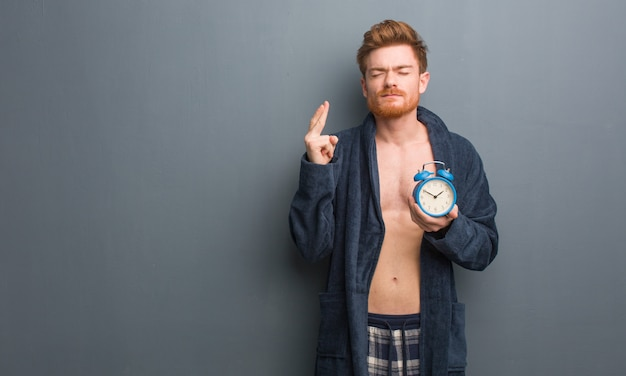 Giovane uomo di redhead che porta le dita dell'incrocio del pigiama per avere fortuna. sta tenendo in mano una sveglia.
