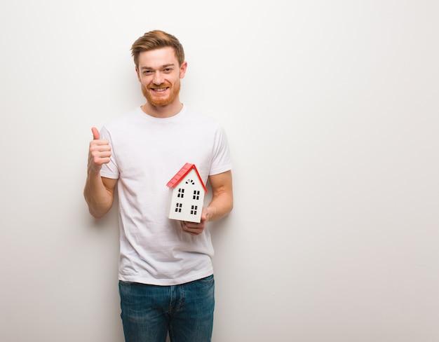 Giovane uomo di redhead che sorride e che alza pollice in su. in possesso di un modello di casa.