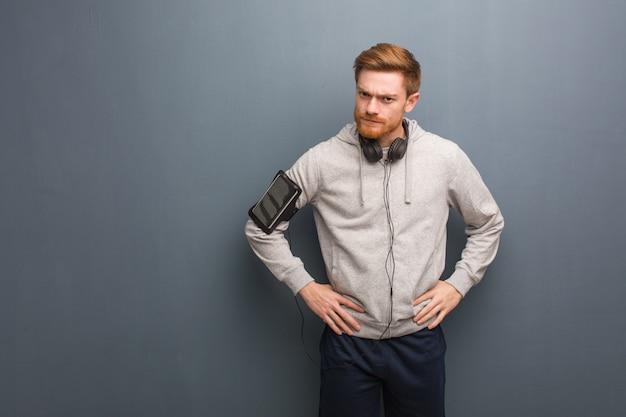 Giovane uomo di redhead di fitness che rimprovera qualcuno molto arrabbiato