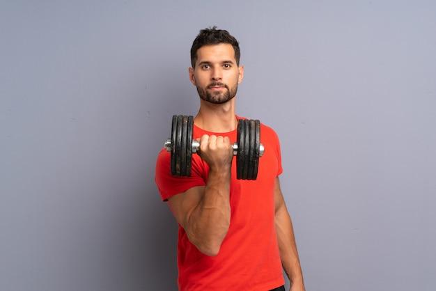 Giovane uomo di sport che fa sollevamento pesi