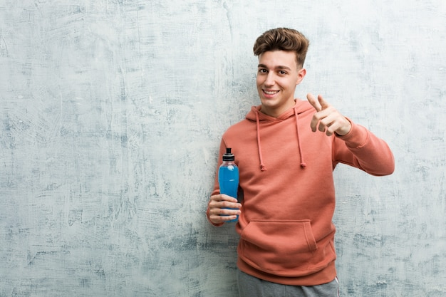 Giovane uomo di sport che tiene un sorriso allegro della bevanda di energia che indica la parte anteriore