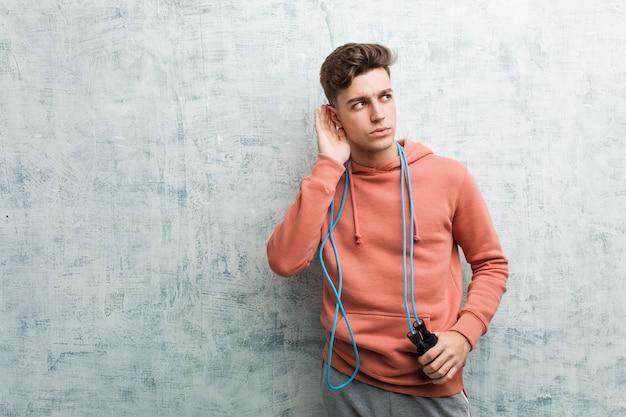 Giovane uomo di sport che tiene una corda per saltare cercando di ascoltare un gossip.