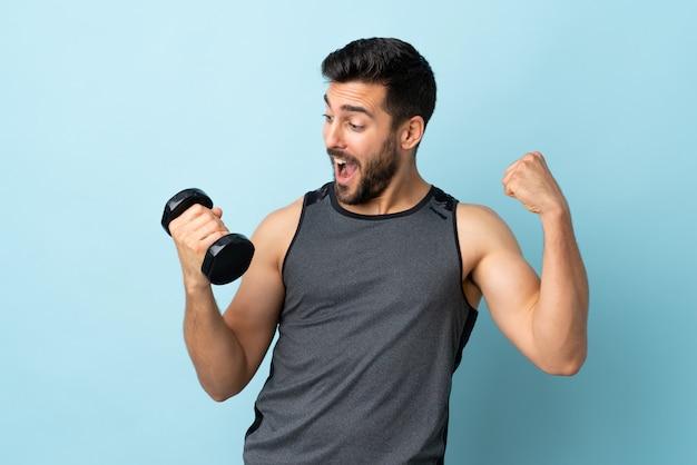 Giovane uomo di sport con la barba che fa sollevamento pesi che celebra una vittoria