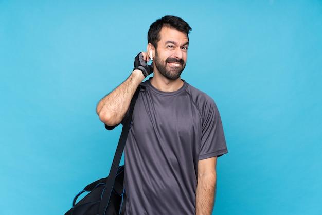 Giovane uomo di sport con la barba sopra la parete blu isolata che ha dubbi