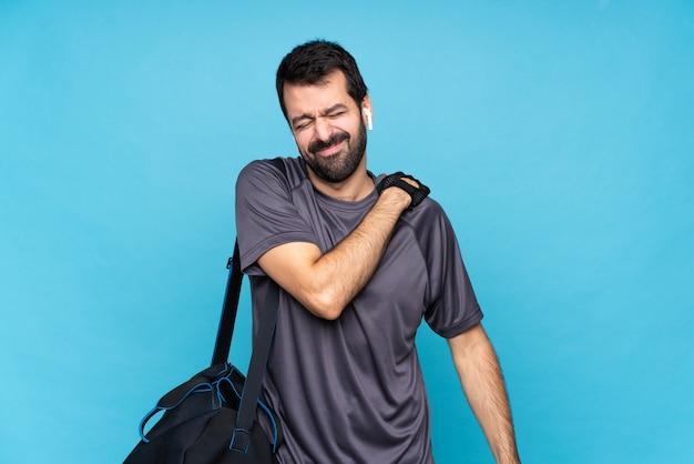 Giovane uomo di sport con la barba sopra la parete blu isolata che soffrono di dolore alla spalla per aver fatto uno sforzo