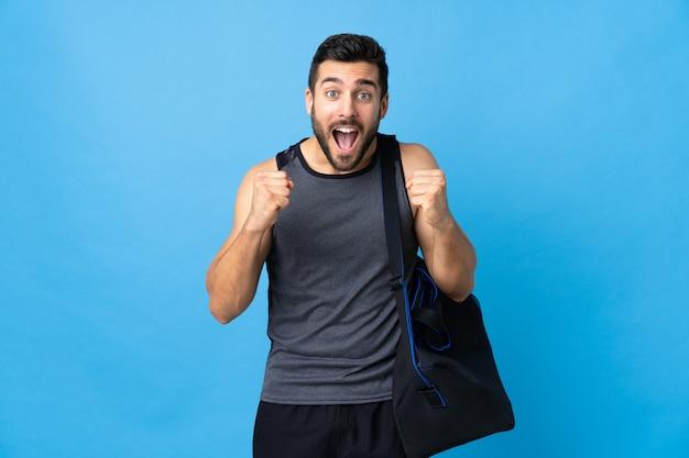 Giovane uomo di sport con la borsa di sport isolata sulla parete blu che celebra una vittoria nella posizione del vincitore