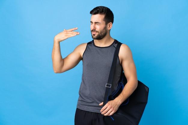 Giovane uomo di sport con la borsa di sport isolata sulla parete blu con l'espressione stanca e malata