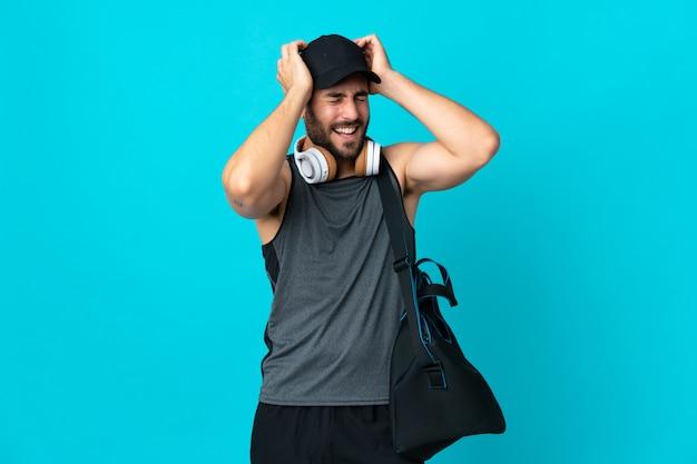 Giovane uomo di sport con la borsa di sport isolata sulla risata blu della parete