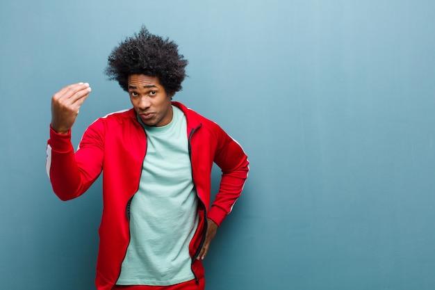 Giovane uomo di sport nero che fa gesti o gesti di denaro, dicendoti di pagare i tuoi debiti! contro il muro del grunge