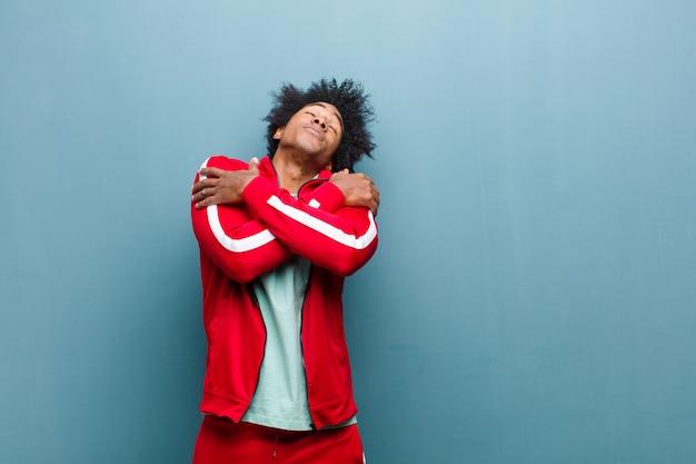 Giovane uomo di sport nero sentirsi innamorato, sorridente, coccole e abbracciarsi, rimanere single, essere egoista ed egocentrico sulla parete del grunge