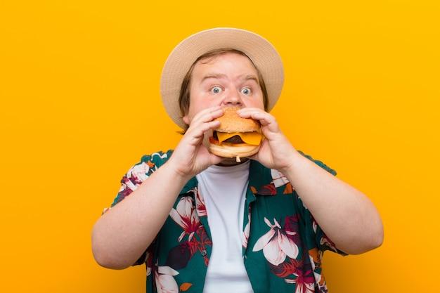 Giovane uomo di taglia grande con un hamburger al formaggio