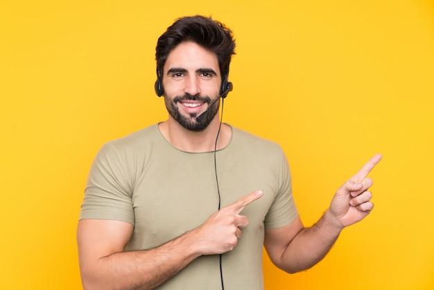 Giovane uomo di telemarketer sopra la parete isolata