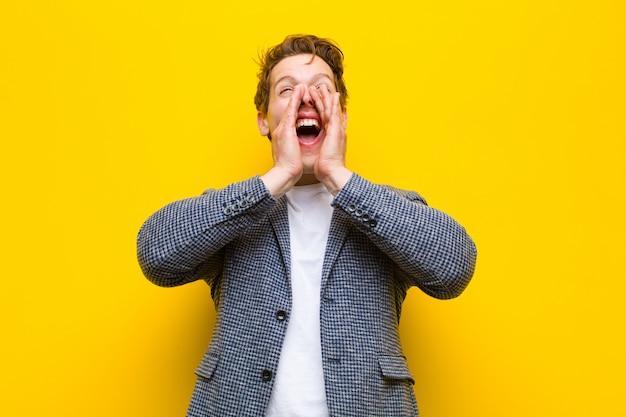 Giovane uomo di testa rosso sentirsi felice, eccitato e positivo, dando un grande grido con le mani vicino alla bocca, chiamando contro l'arancia