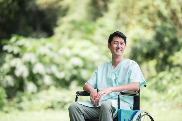Giovane uomo disabile da solo in sedia a rotelle al giardino