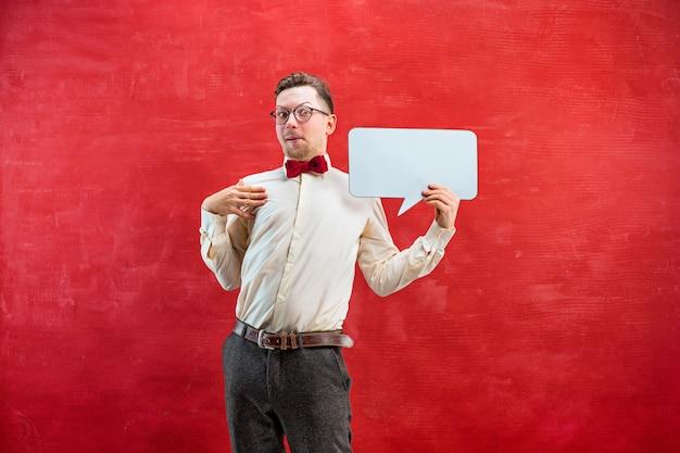 Giovane uomo divertente deluso con segno in bianco vuoto su sfondo rosso studio con spazio di copia