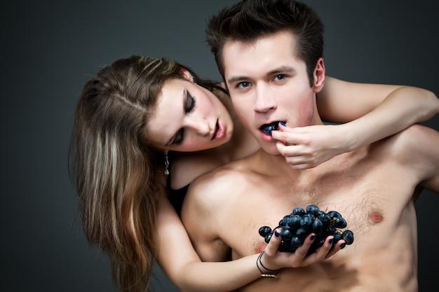 Giovane uomo divertente sorridente che mangia uva nera con la sua ragazza nuda