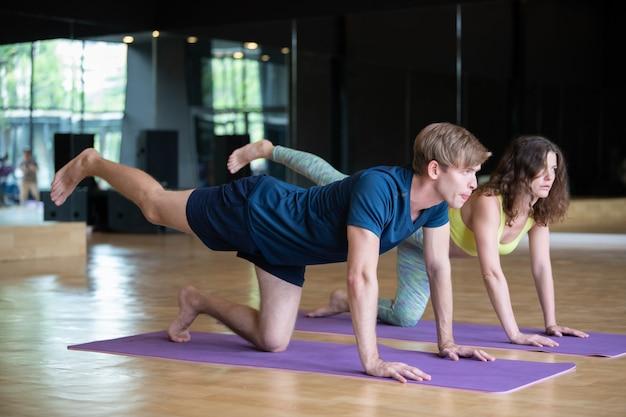 Giovane uomo e donna caucasici nell'allenamento di forma fisica dell'aula di yoga
