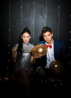 Giovane uomo e donna con palloncini seduto sulla panchina