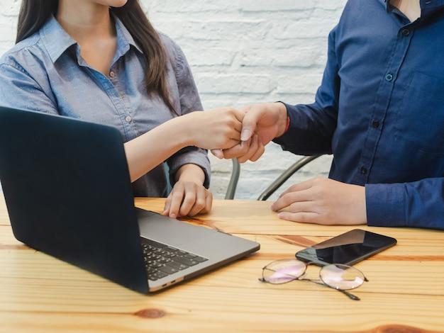 Giovane uomo e donna di affari che agitano le mani per coworking.