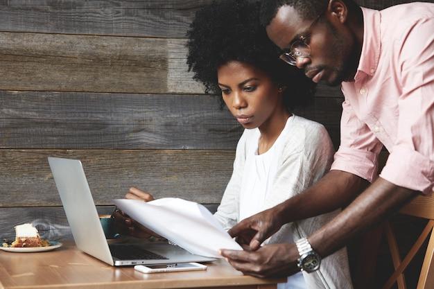 Giovane uomo e donna nella caffetteria utilizzando laptop