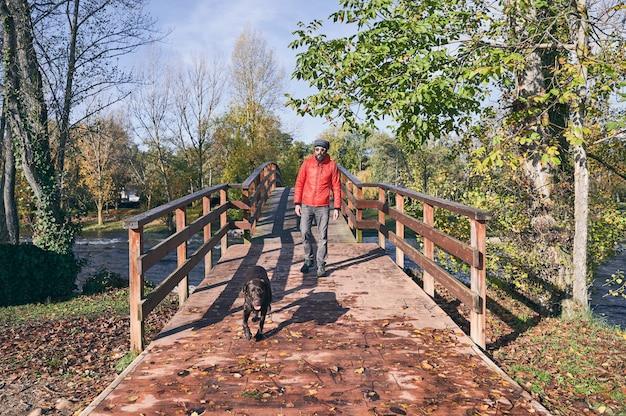 Giovane uomo e il suo cane che attraversano un ponte in una fredda mattina d'autunno.