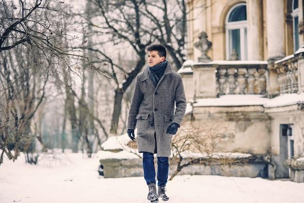 Giovane uomo elegante in caldo cappotto grigio e guanti di pelle che cammina per strada innevata