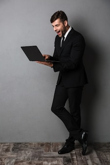 Giovane uomo emozionante felice di affari che per mezzo del computer portatile
