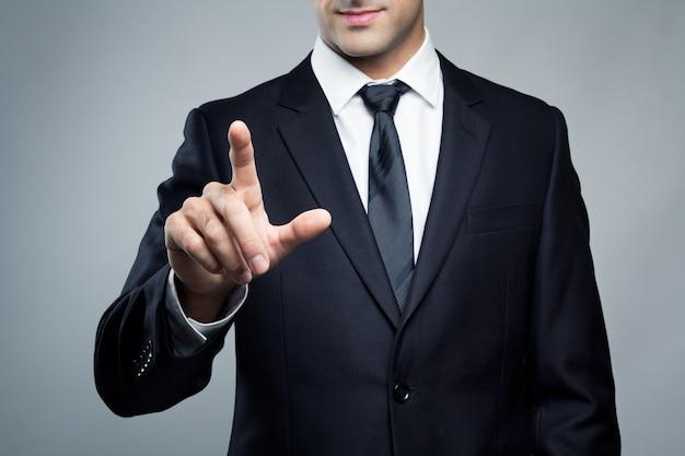 Giovane uomo esecutivo che tocca uno schermo immaginario