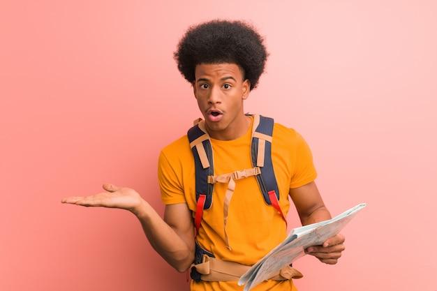 Giovane uomo esploratore afroamericano che tiene una mappa che tiene qualcosa sulla mano della palma