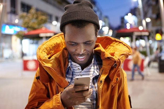 Giovane uomo europeo nero attraente in messaggio di testo di battitura a macchina dell'abbigliamento di inverno sul suo cellulare, stante nella regolazione della città di notte. sms di lettura maschio dalla pelle scura gioiosa