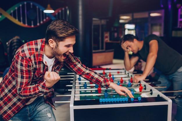 Giovane uomo felice barbuto che incoraggia al tavolo da calcio nella stanza da gioco. lui vince. un altro ragazzo sta dietro. sembra sconvolto.
