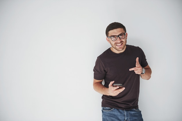 Giovane uomo felice casual vestito con smart phone su bianco