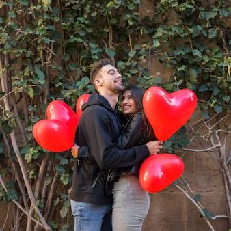 Giovane uomo felice che abbraccia la donna sorridente e azienda palloncini in forma di cuori