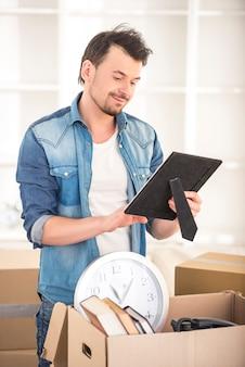 Giovane uomo felice che mette le cose in una scatola.