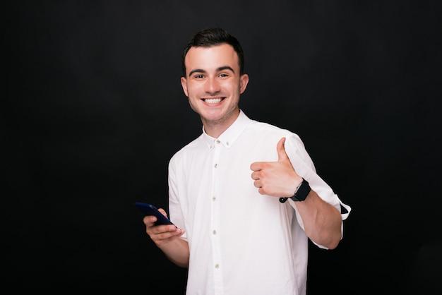 Giovane uomo felice che mostra pollice in su e che tiene il suo telefono. gli piace!