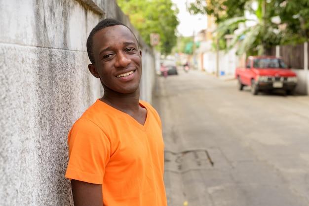 Giovane uomo felice che sorride mentre pensando e appoggiandosi contro il vecchio muro di cemento nelle strade all'aperto