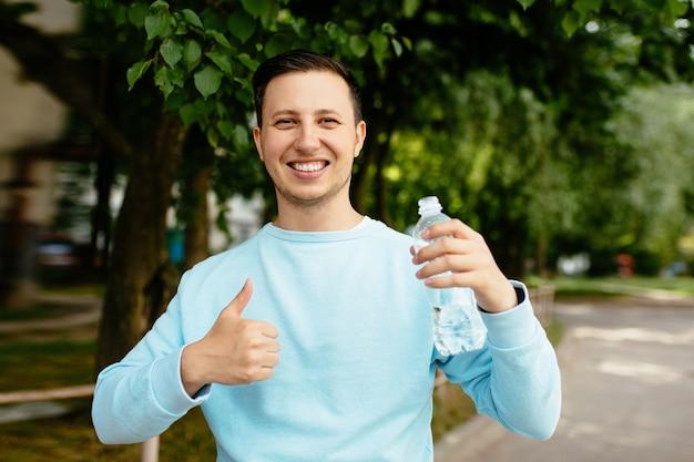 Giovane uomo felice con la bottiglia di acqua nella sua mano che sorride e che mostra i pollici su