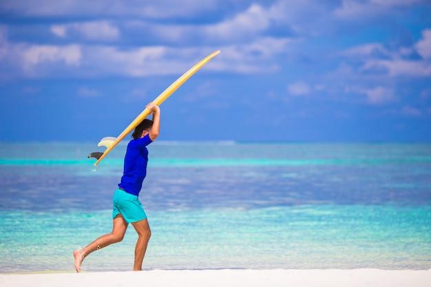 Giovane uomo felice del surf alla spiaggia bianca con il surf giallo