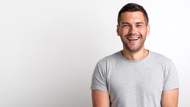 Giovane uomo felice della stoppia che ride e che controlla contesto bianco
