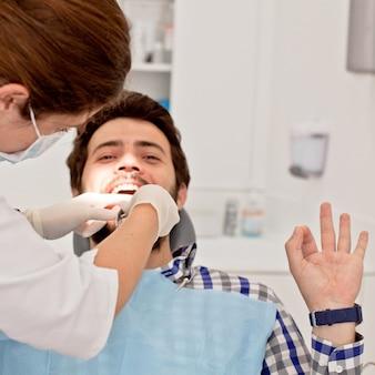 Giovane uomo felice e donna in una visita odontoiatrica al dentista